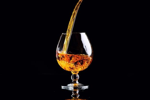 Vetro con cognac su fondo nero