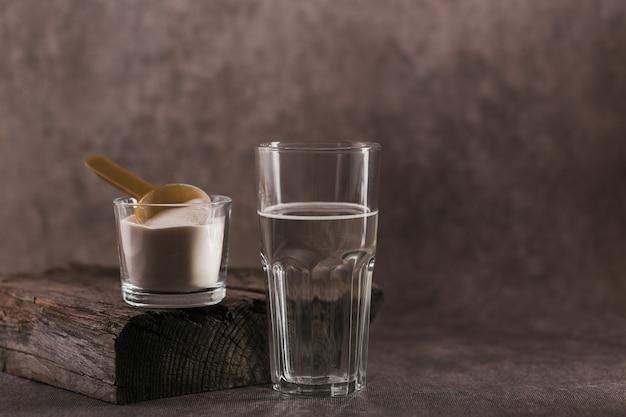 Vetro con collagene sciolto in acqua e polvere proteica di collagene su colore marrone