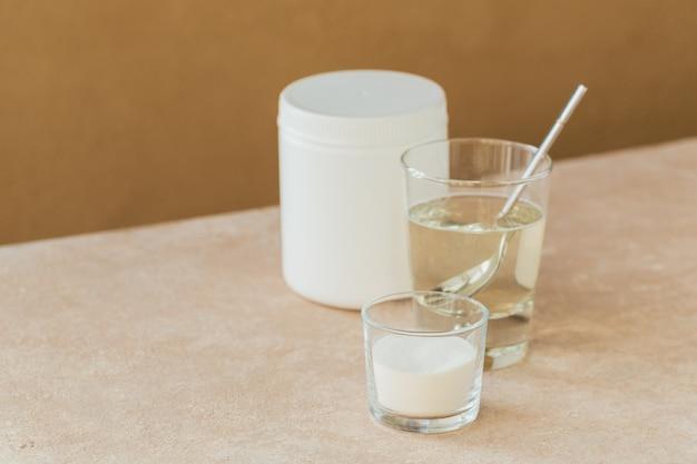 Vetro con collagene sciolto in acqua e polvere di proteine di collagene su un tavolo beige chiaro.