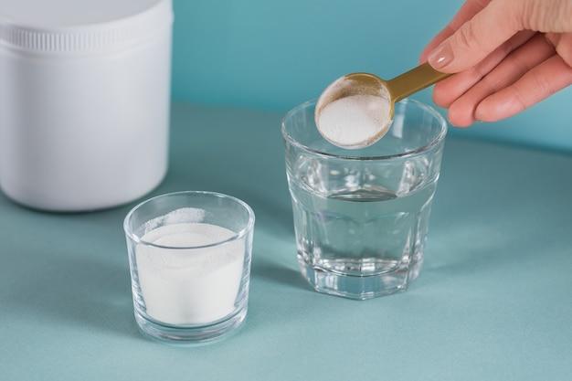 Vetro con collagene sciolto in acqua e polvere di proteine di collagene su azzurro
