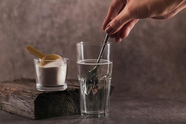 Vetro con collagene sciolto in acqua e polvere proteica di collagene. la mano della donna tiene un cucchiaio. concetto di stile di vita sano.