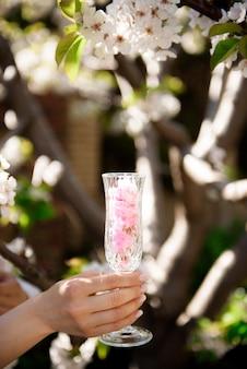 Un bicchiere con fiori all'interno sullo sfondo di un giardino primaverile in fiore.