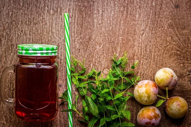 Bicchiere con succo di prugna fresca e menta verde su fondo in legno vintage