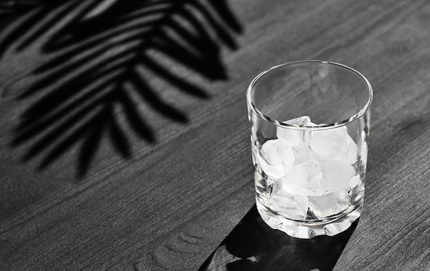 Vetro con ghiaccio su un fondo di legno nero con lo spazio della copia. l'idea di preparare una bevanda rinfrescante al caffè estivo, luce solare intensa, ombra di foglie di palma
