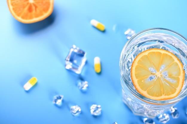 Bicchiere con acqua ghiacciata e limone vitamina c soft focus selettivo