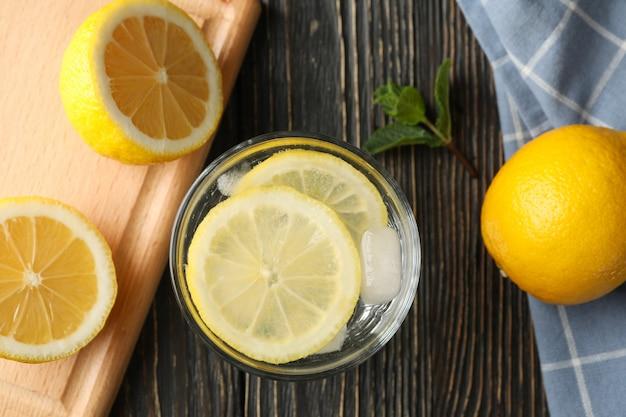 Vetro con limonata e ingredienti su superficie di legno, vista dall'alto