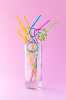 Vetro con molte cannucce colorate di plastica su uno sfondo rosa, concetto di umore divertente. astrazione, design conciso creativo.