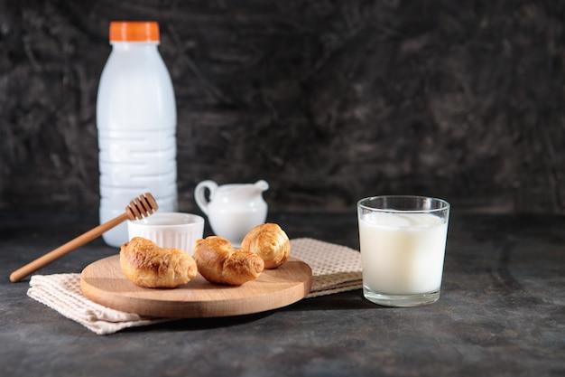 Vetro con latte e cornetti con miele su sfondo nero. gustosa colazione francese. dolce. spazio per il testo