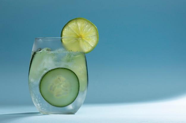 Bicchiere con acqua minerale e ghiaccio con fette di cetriolo e limone su sfondo blu