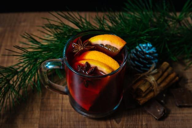 Bicchiere con vin brulé su un tavolo di legno con rami di abete capodanno. decorazioni natalizie con bevande calde invernali tradizionali