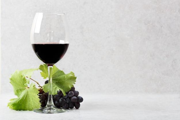 Bicchiere di vino rosso e uva su un tavolo di pietra. sfondo grigio chiaro.