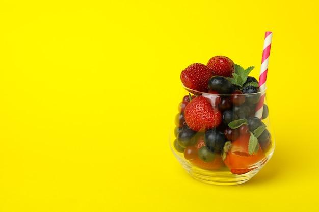 Bicchiere con ingredienti frullato su sfondo giallo