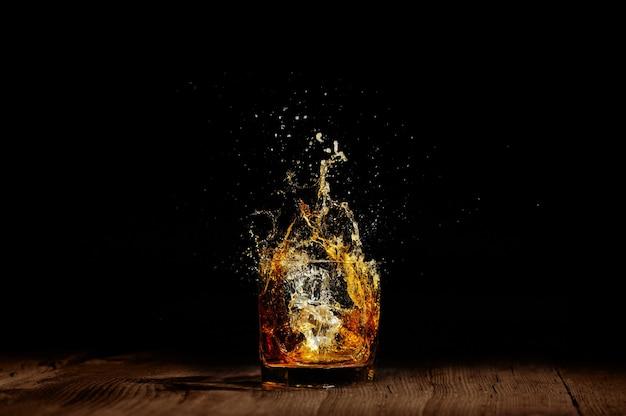 Vetro con schizzi di cognac sul tavolo di legno.