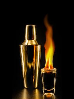 Bicchiere con colpi di tequila in fiamme, bevanda fiammeggiante