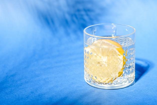 Vetro con acqua e limone sulla superficie blu con ombra di foglia di palma tropicale