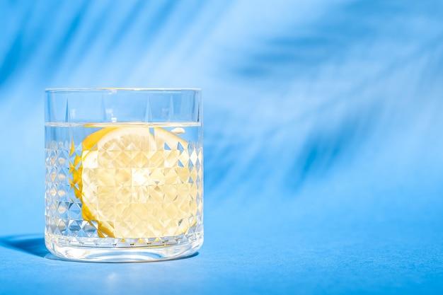 Vetro con acqua e limone sulla parete blu con ombra di foglia di palma tropicale