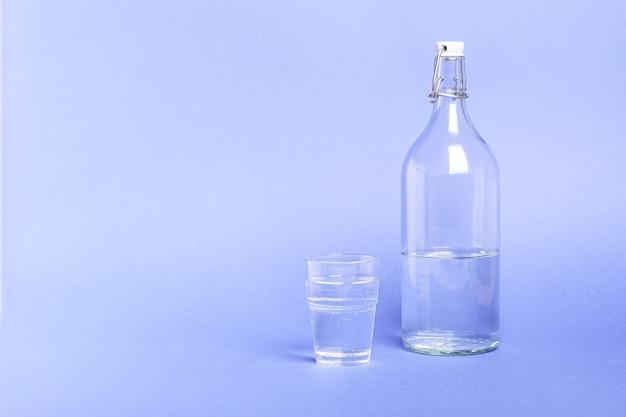 Vetro con acqua vicino alla bottiglia sulla superficie blu