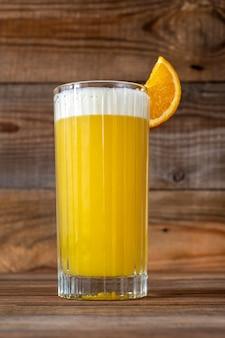 Bicchiere di yellow bird cocktail guarnito con fetta d'arancia