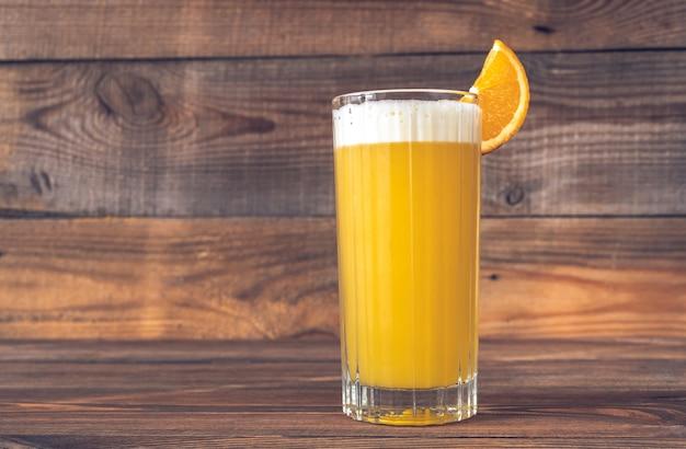 Bicchiere di yellow bird cocktail guarnito con fetta d'arancia orange