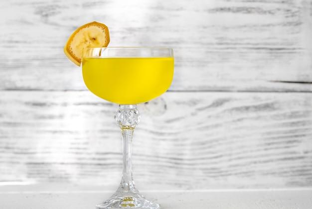 Bicchiere di yellow submarine cocktail guarnito con fetta di banana