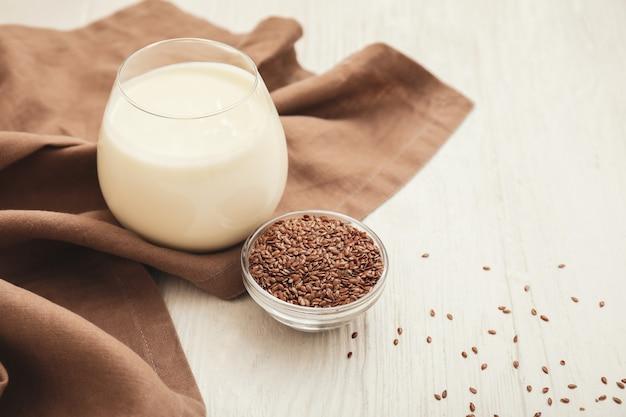 Bicchiere di yogurt e semi di lino sul tavolo bianco