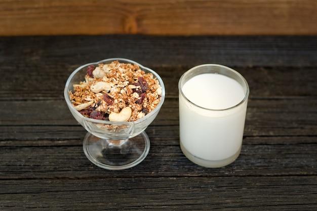 Bicchiere di yogurt e muesli su un tavolo di legno nero