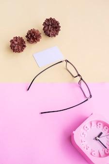 Occhiali, sveglia, fiori di pino su uno sfondo rosa pastello e giallo pastello. concetto estivo, concetto minimale