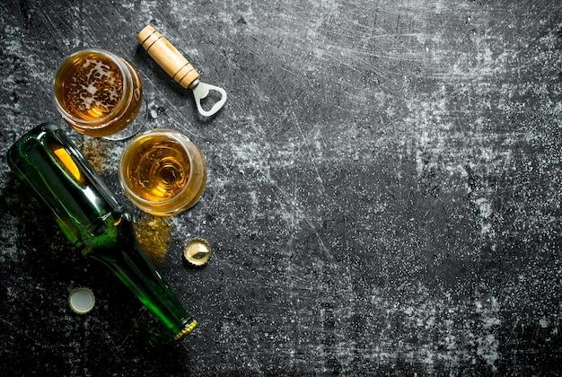 Bicchieri di birra e apriscatole. su sfondo nero rustico