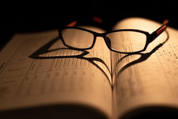 Occhiali sul libro su sfondo scuro.