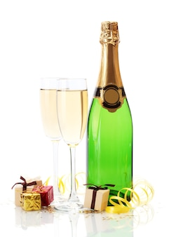 Bicchieri e bottiglia di champagne, regali e serpentine isolati su un bianco