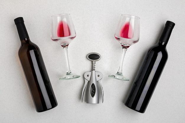 Bicchieri e bottiglie di vino rosso e bianco su sfondo bianco dalla vista dall'alto. copia spazio