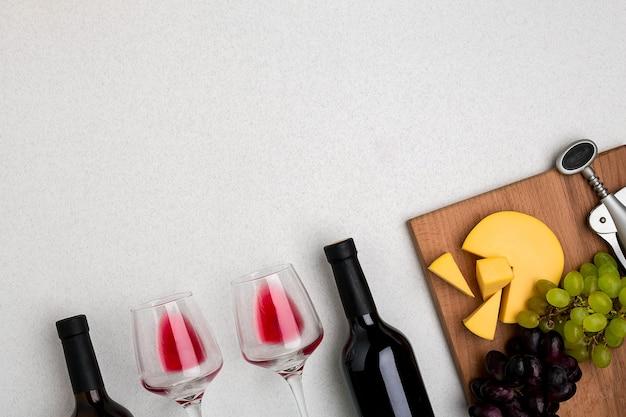 Bicchieri e bottiglie di vino rosso e bianco su sfondo bianco dalla vista dall'alto