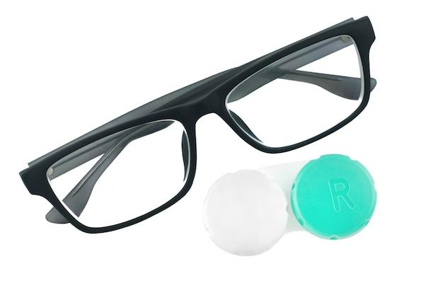 Occhiali e una scatola di lenti ottiche giacciono su un bianco