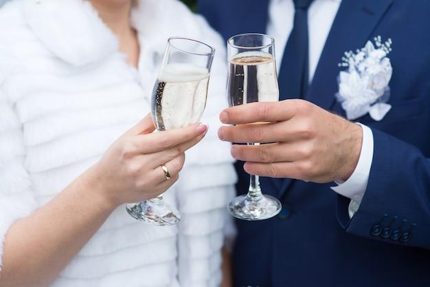 Bicchieri del primo piano della sposa e dello sposo con champagne