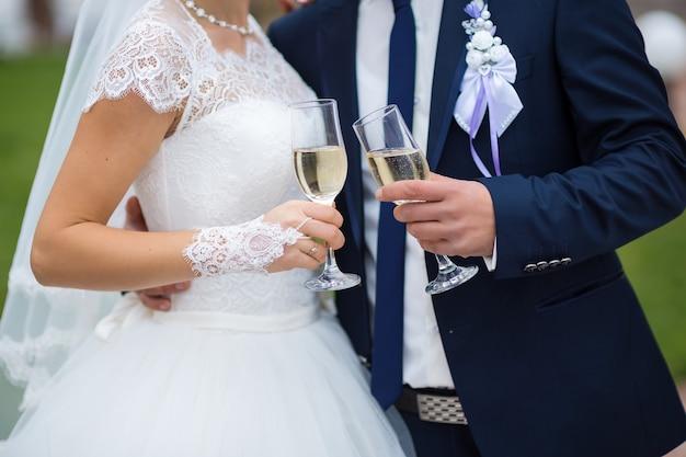 Bicchieri della sposa e dello sposo nelle mani in primo piano con champagne