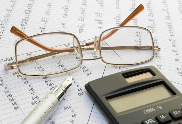 Primo piano di vetro, del calcolatore e della penna