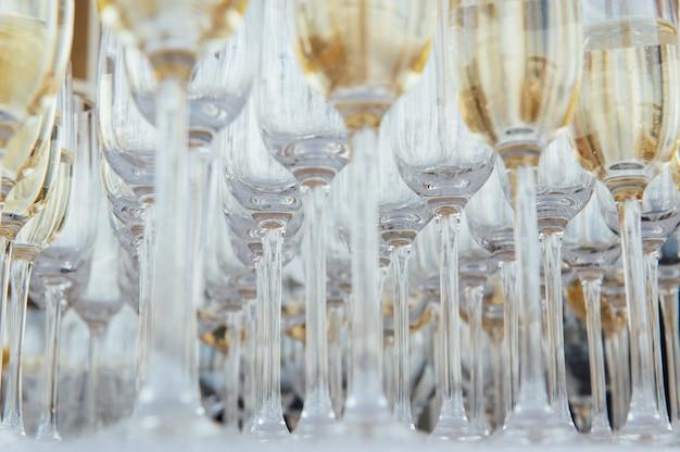 Bicchieri di champagne al banchetto, spumante bianco in bicchieri di vino, atmosfera festosa.