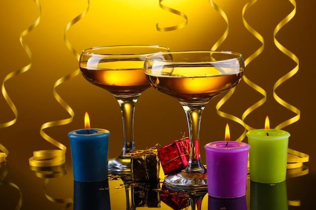 Bicchieri di champagne, candele, regali e stelle filanti su sfondo giallo