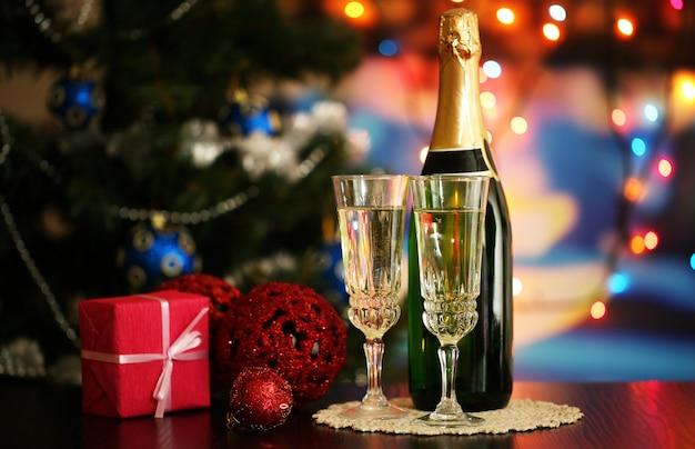 Bicchieri di champagne e regalo su sfondo luminoso