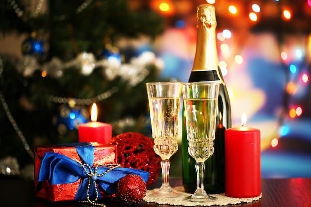 Bicchieri di champagne e regali su sfondo luminoso