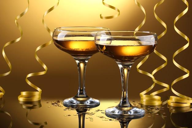 Bicchieri di champagne e stelle filanti su sfondo giallo