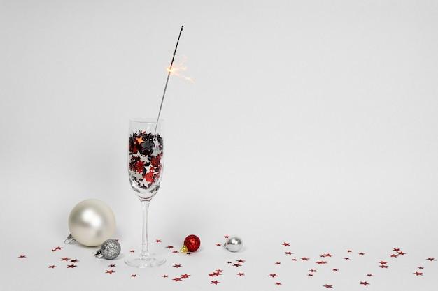 Bicchieri di champagne con coriandoli a forma di stelle e sparkler