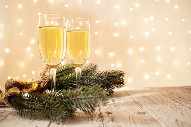 Bicchieri di champagne su un tavolo di legno con una ghirlanda dorata sfocata, concetto di capodanno
