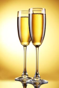 Bicchieri di champagne su sfondo giallo