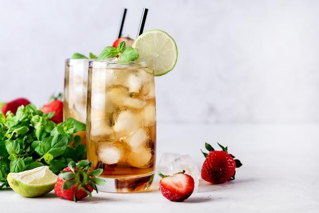 Bicchieri di agrumi freddi e tè freddo alla fragola su sfondo grigio chiaro