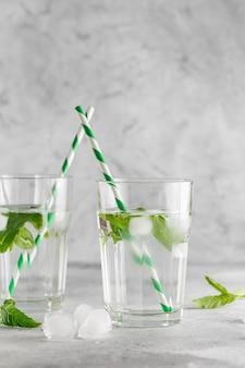 Bicchieri di acqua fredda con foglie di menta fresca e cubetti di ghiaccio su cemento grigio