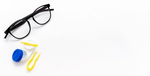 Occhiali, lenti a contatto, pinzette e un applicatore per prendere una lente da una custodia su un bianco.