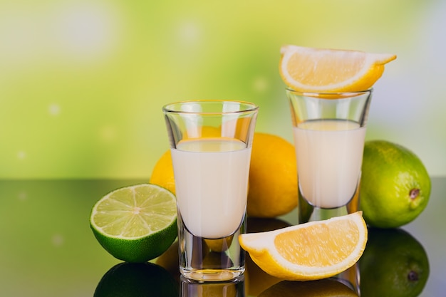 Bicchieri di liquore alla crema con lime e limone su sfondo verde con la riflessione. a corto di liquore al limone. bevanda alcolica tradizionale italiana limoncello