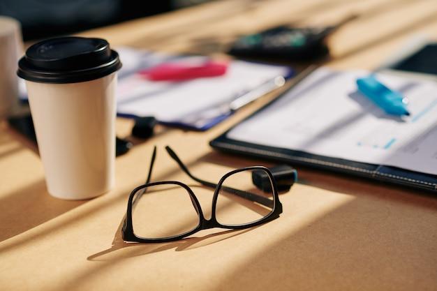 Bicchieri e tazza di caffè da asporto sul tavolo dell'ufficio con due contratti