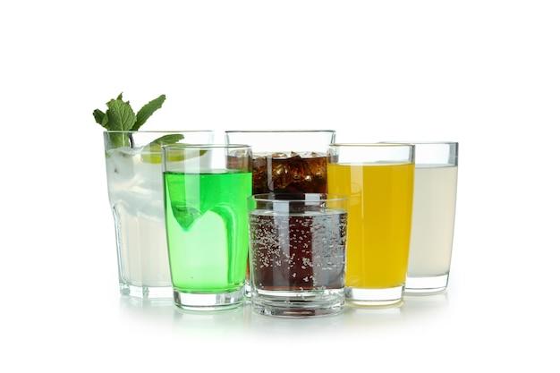 Bicchieri di soda differenti isolati su superficie bianca